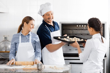 toque blanche: Happy Chefs Baking At Commercial Kitchen Stock Photo