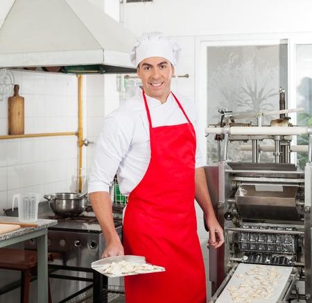 cocinas industriales: Confiado Cocinero que prepara los raviolis de pasta en la máquina