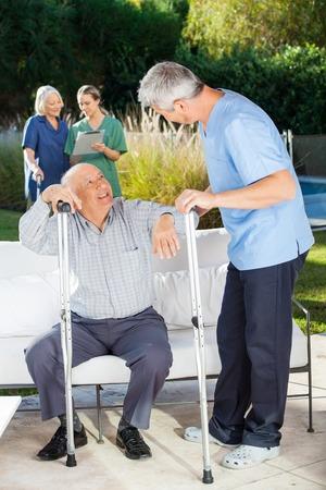 ancianos caminando: Los cuidadores masculinos y femeninos Ayudando a las Personas Mayores