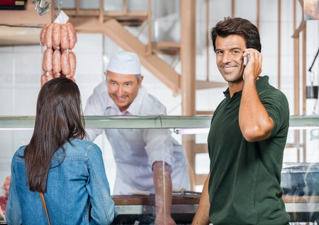 Happy Man On Call While Woman Buying Meat photo