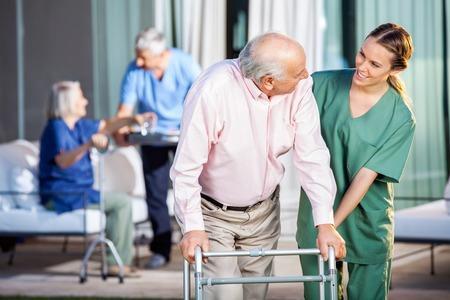 Gelukkig Caretaker Assisteren Senior Man in het gebruik van Zimmer Frame