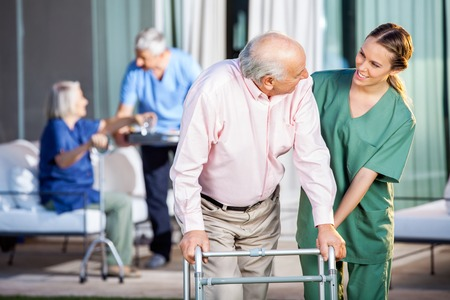 elderly adults: Happy Caretaker Assisting Senior Man In Using Zimmer Frame