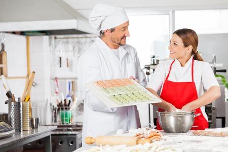 Smiling Chefs Preparing Ravioli Pasta In Kitchen photo