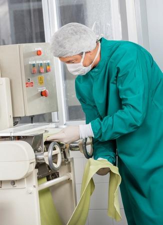 workwear: Chef In Protective Workwear Using Spaghetti Pasta Machine
