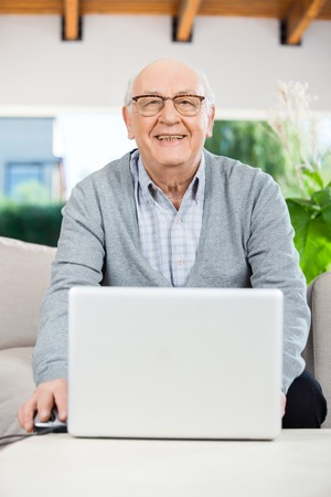 mobility nursing: Happy Senior Man With Laptop At Nursing Home Porch