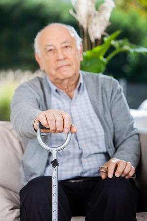 Portrait Of Elderly Man Holding Metal Cane photo