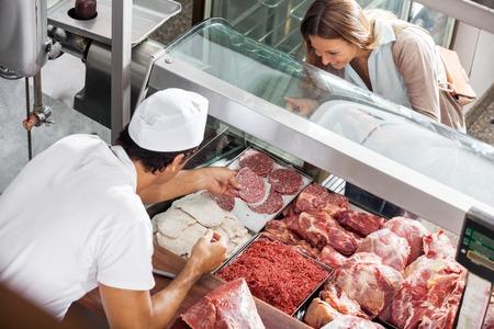 Carnicería: Carnicero Mostrando Carne al Cliente en Carnicería