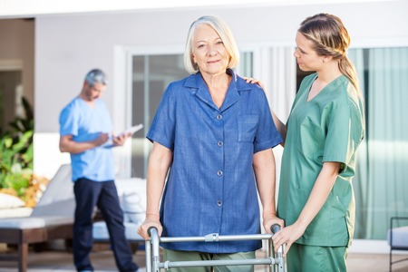enfermeras: Enfermera asiste a la mujer mayor a recorrer con el cap�tulo Zimmer Foto de archivo