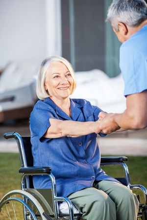 assisted: Senior Woman On Wheelchair Being Assisted By Nurse Stock Photo