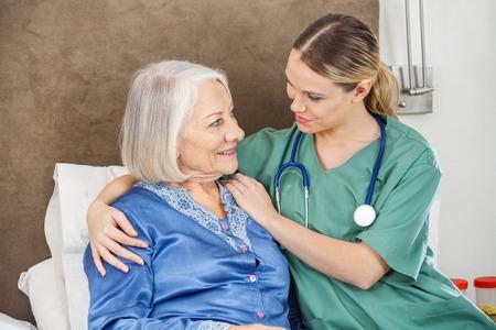 residents: Female Caretaker Comforting Senior Woman Stock Photo