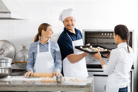 toque blanche: Smiling Chef Taking Baking Sheet From Colleague By Oven
