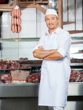 Butcher Standing Arms Crossed In Butchery photo