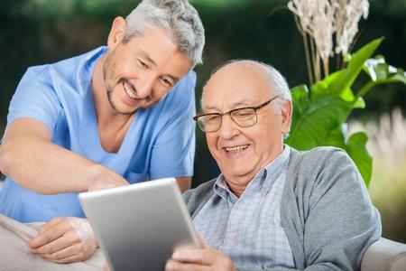 Infermiera E anziano che gode durante l'utilizzo di Tablet Computer
