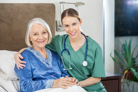 Happy Caretaker With Arm Around Senior Woman At Nursing Home Stock Photo