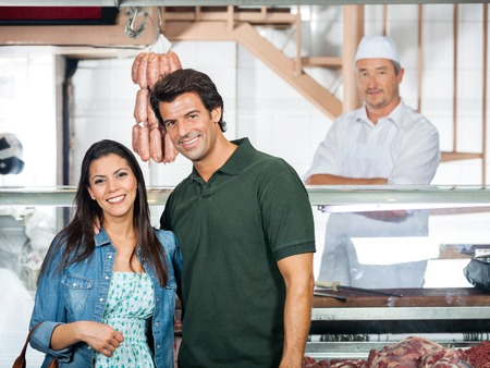 Happy Couple Standing In Butcher Shop photo