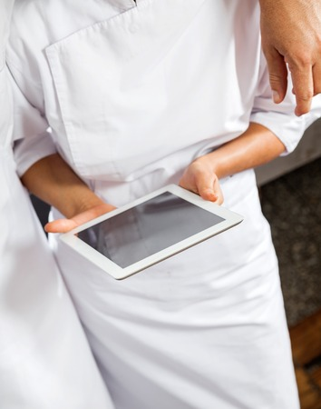 midsection: Midsection Of Butchers Using Digital Tablet