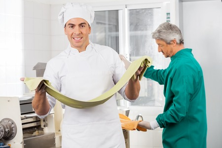 toque blanche: Confident Chef Holding Pasta Sheet With Colleague Working In Bac