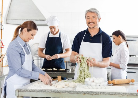 ribbon pasta: Smiling Male Chef With Colleagues Preparing Pasta In Kitchen