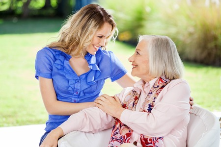 home visit: Affectionate Granddaughter And Grandmother At Nursing Home Porch Stock Photo