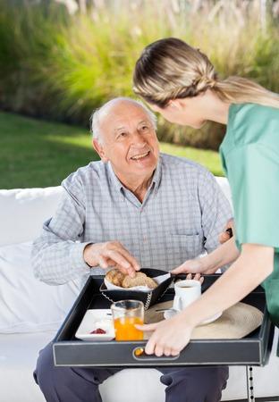 Female Caretaker Serving Breakfast To Senior Man Stockfoto