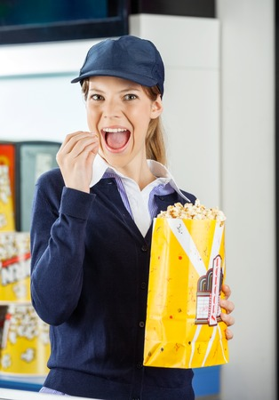 concession: Worker Eating Popcorn At Cinema Concession Stand