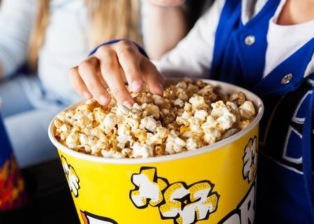 Muchacha que come las palomitas en el cine Teatro Foto de archivo