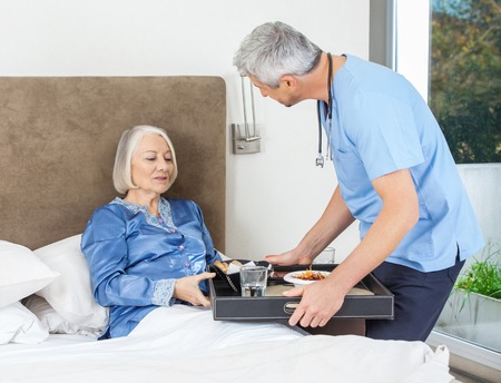 Nurse Serving Breakfast To Senior Woman On Bed photo