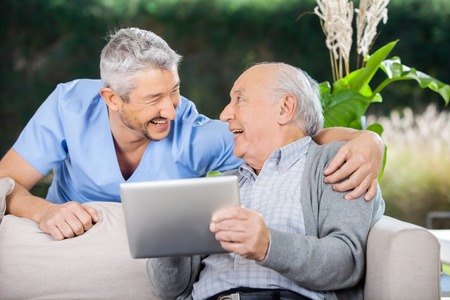 enfermera: Riendo Caretaker Y Hombre mayor que usa la computadora de la tableta Foto de archivo