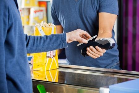 palomitas de maiz: Hombre que usa la tecnolog�a NFC para efectuar el pago en el cine