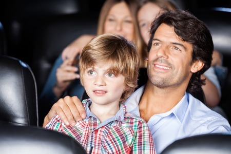 love movies: Father And Son Watching Film In Theater