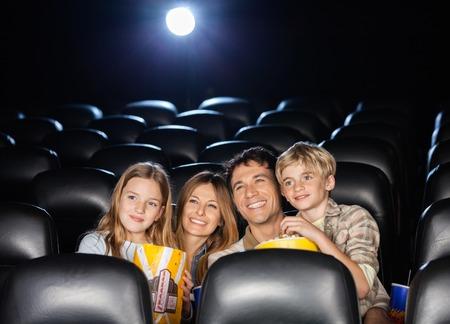 palomitas: Familia feliz que mira Cine En Teatro Foto de archivo