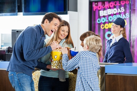 concession: Playful Family Enjoying Snacks At Cinema Concession Stand Stock Photo