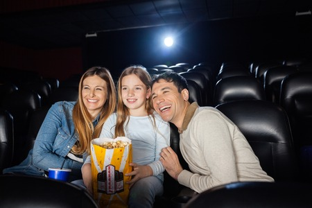 father daughter: Cheerful Family Enjoying Film In Theater Stock Photo