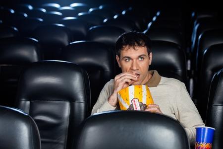 popcorn: El hombre que come las palomitas mientras ve la pel�cula En Teatro Foto de archivo