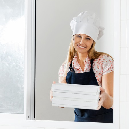 Happy Chef Holding Packed Pasta Boxes At Window photo