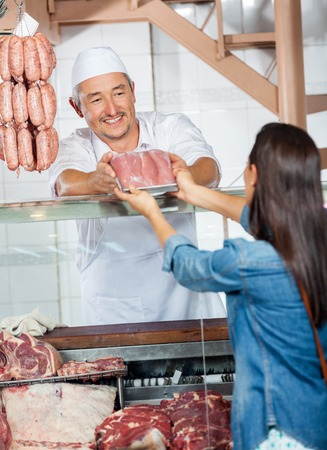 meat counter: Man Selling Fresh Packed Of Sausages To Customer