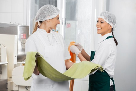 conversing: Happy Chefs Conversing While Holding Pasta Sheets