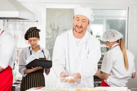 sprinkling: Male Chef Sprinkling Flour On Ravioli Pasta In Kitchen