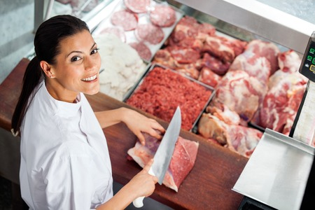 Happy Female Butcher Cutting Meat At Butchery Stok Fotoğraf
