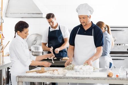 toque blanche: Chefs Preparing Pasta At Kitchen Counters