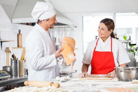 toque blanche: Happy Chefs Preparing Pasta At Kitchen Counter