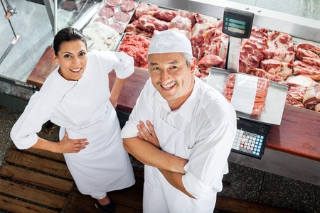 Confident Butchers Standing At Butchery Counter