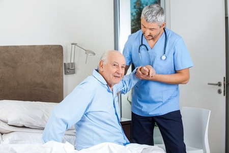 Senior Man Being Assisted By Male Caretaker In Bedroom Stock Photo