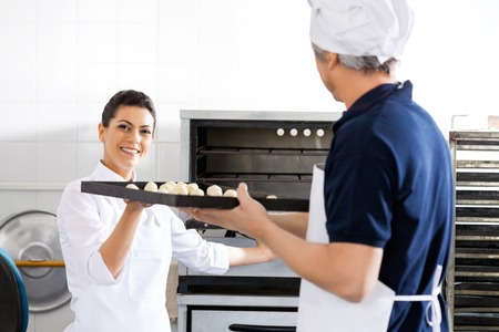 toque blanche: Smiling Chef Taking Baking Sheet From Colleague In Kitchen Stock Photo
