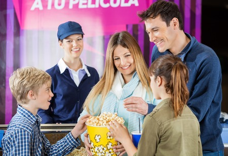 concession: Happy Family Enjoying Popcorn At Cinema Concession Counter