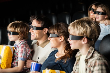 3d: Happy Families Watching 3D Movie In Theater Stock Photo