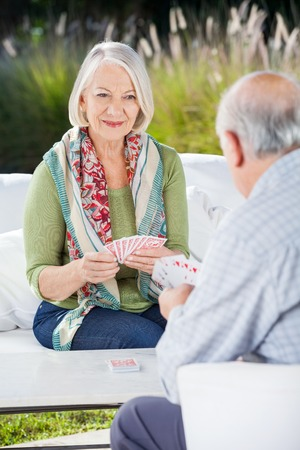 eldercare: Senior Woman Playing Cards With Man Stock Photo