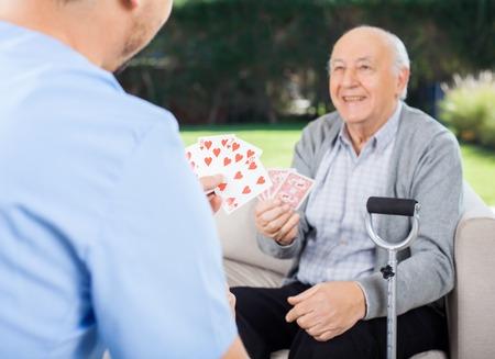 eldercare: Caretaker And Senior Man Playing Cards At Nursing Home