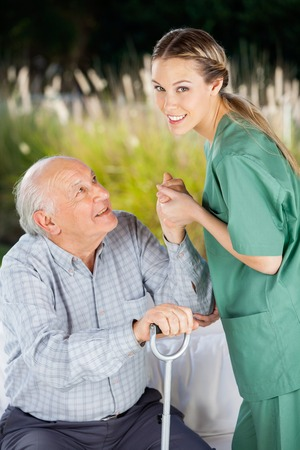 get up: Smiling Nurse Helping Senior Man To Get Up From Couch Stock Photo