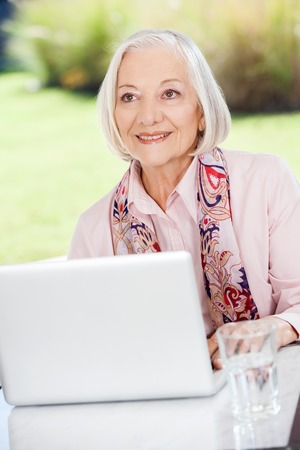 Smiling Elderly Woman Looking Away While Using Laptop On Porch photo